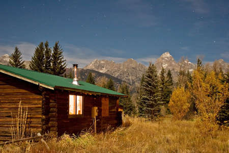 warmly: Mountain log cabin glowing warmly at night Stock Photo