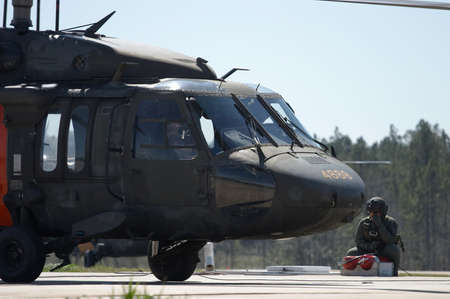blackhawk helicopter: A military pilot observes as a Blackhawk helicopter is refueled Stock Photo