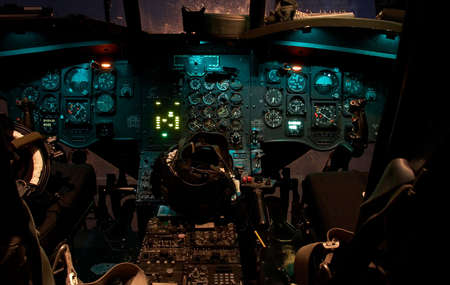 The cockpit of a Chinook helicopter at night with lights glowing