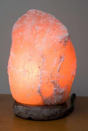 Een zout lamp zit op een bureau, ingeschakeld Stockfoto