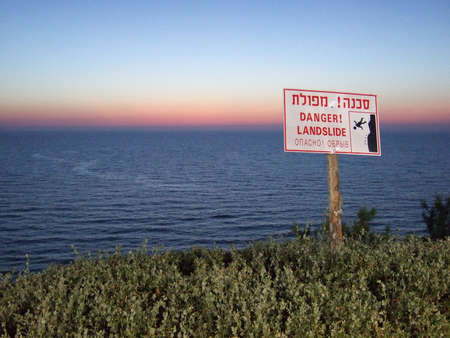 multilingual: Cliff danger sign over the water, written in Hebrew, English, and Russian