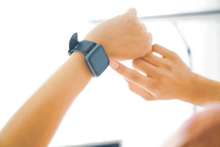 A woman watching a smartwatch in her office 写真素材