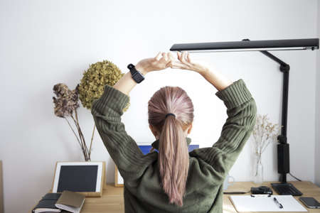 A woman taking a break by stretching her stretch in the office
