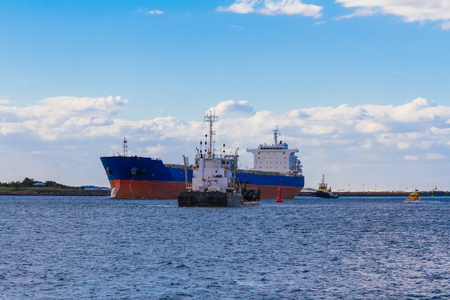 towing: Cargo Ship is towing into the harbor of Newcastle