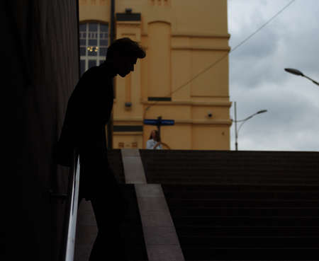 dark outline of a man, siluet, with his head bowed, on the steps, concept