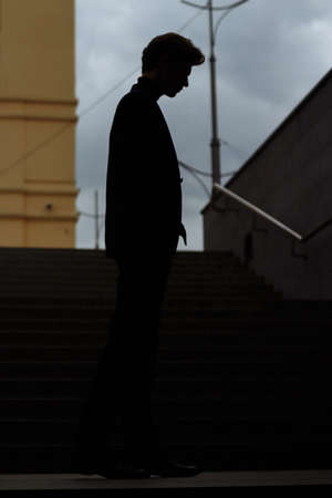 dark outline of a man, siluet, with his head bowed, on the steps, concept Banco de Imagens