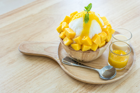 black dish: Bingsu ( Korea food) with mango on table