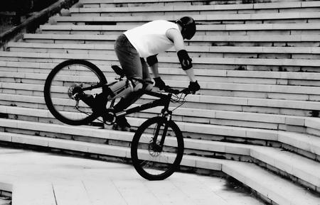 mountain biker performing stunt black and white