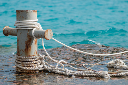 mooring bollard: Rusty mooring bollard with ship ropes and  clear turquouse sea ocen water on background.