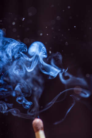 ember: Match with smoke on black background. With copyspace