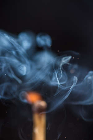 ember: Match with smoke and fire on  the black background.  copyspace