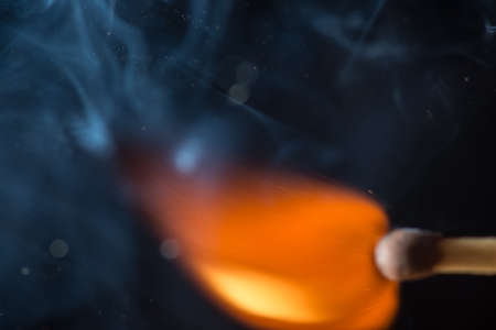 Match with smoke and fire on  the black background.  copyspace