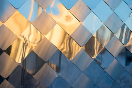 similar: old, dirty aluminum metal wall facade panel with rhombus, similar to the scales and tiles. Reflection of sunset Stock Photo