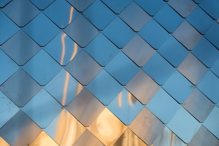 door casing: old, dirty aluminum metal wall facade panel with rhombus, similar to the scales and tiles. Reflection of sunset Stock Photo