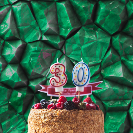 raspberries blackberry birthday cake with candles number 30 on stone background and copyspace Stock Photo