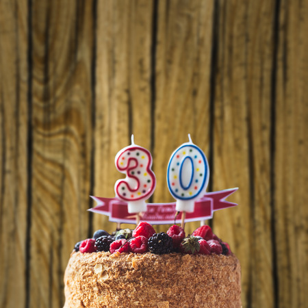 raspberries blackberry birthday cake with candles number 30 on wood background and copyspace