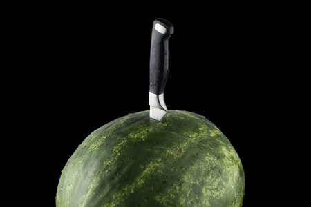 isolated Riped watermelon with knife and black background.