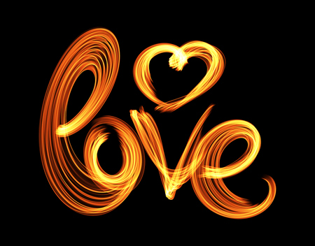 Love isolated word lettering and heart written with fire flame or smoke on black background.
