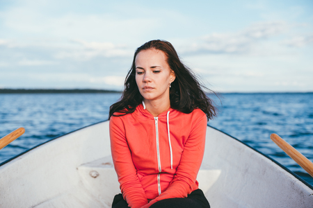 amazing beautiful haired girl swims on a wooden boat and rowing with oars in the gorgeous spring lake. Lifestyle without makeup