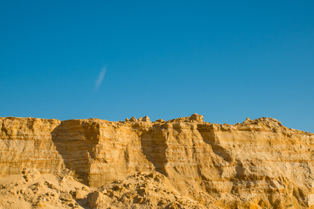 cliff of the yellow orange brown sand soil clay under the bright sunny day with deep blue sky Stock Photo