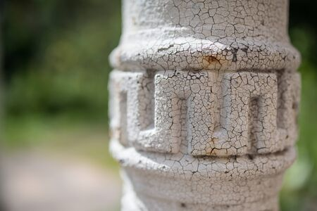 detail of old metallic supporting greek style column in brick wall Stock Photo