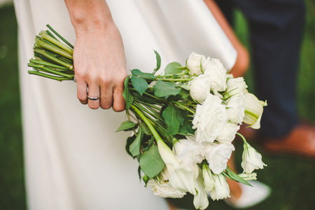 wedding bouquet of gorgeous white roses at brides hand