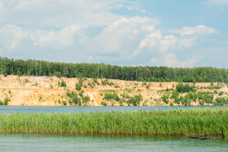 sand quarry: Blue lake with the orange yellow sand hills mountain and forest on top against sky