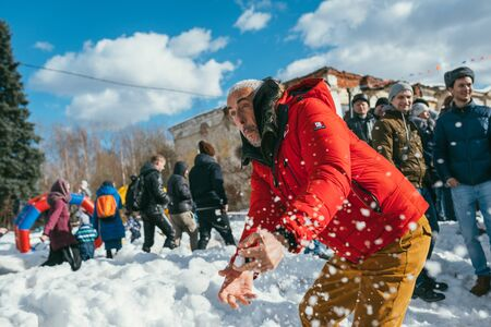 MOSCOW REGION, FRYAZINO, GREBNEVO ESTATE - MARCH 09 2019: Larbi Bibi Naceri French star, actor and director playing snowballs with local kids visiting the Grebnevo estate during Maslenitsa celebration Stockfoto - 136770560