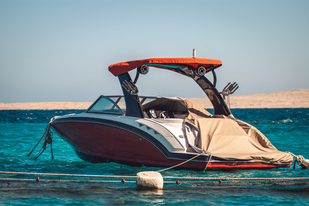 elegant Red Luxury motor boat on the background of the azure blue sea and a strip of sandy mountains in the background
