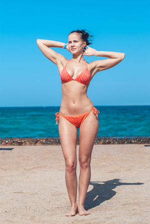 perfectly built Beautiful and young girl with wide hips in a striped orange swimsuit stands and Tans by placing her elbows in the sides against the backdrop of the blue sea. Vertical image