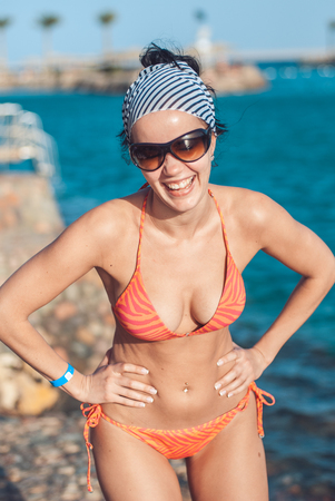 perfectly built Beautiful and young girl with wide hips in a striped orange swimsuit and sunglasses stands and Tans against the backdrop of the blue sea. she laughs showing her teeth.