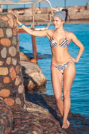 perfectly built Beautiful and young girl with wide hips in a striped swimsuit stands and Tans against the backdrop of the blue sea. she smiles Banco de Imagens