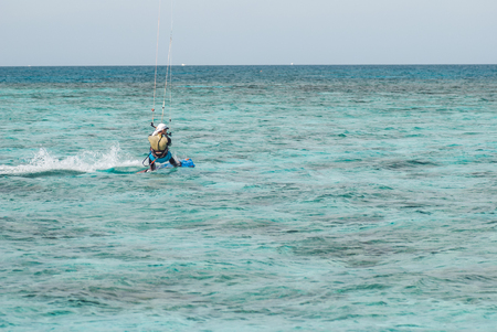 professional kiter glide the water surface of the ocean at great speed. Back view behind wide shot Banco de Imagens