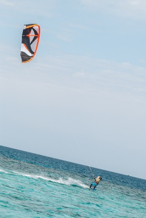 professional kiter glide the water surface of the ocean at great speed. Back view behind extreme wide shot Stok Fotoğraf