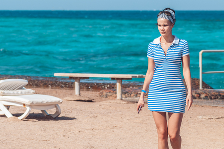 Beautiful and young girl in a striped blue dress walks against the backdrop of the blue sea with a small stripe the sky. She looks away from the camera where there is Free space for your text