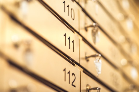 Row of golden numbered lockers with keys - shiny stainless steel metal for keep mail or something important. Selective focus macro shot with shallow depth of field Stok Fotoğraf