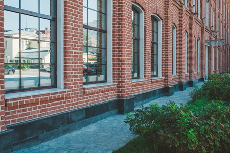Office building in loft style. Large Windows. Red brick wall. Green bushes on the right. Perspective shot composition