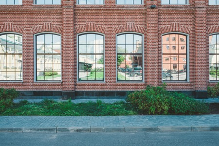 Office building in loft style. Large Windows. Red brick wall. Green bushes on the middle. Flat fasade composition