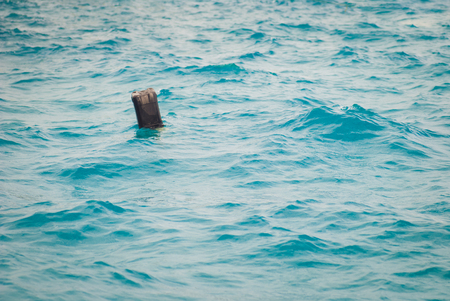 Black plastic canister floats in the sea. Household waste, concept of lack of respect for the environment
