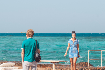 Beautiful and young girl in a striped blue dress walks against the backdrop of the blue sea. Free space for your text. in the foreground is a man who has his back to us and looks into the distance