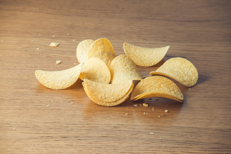 Delicious potato chips, laying on wooden table background Stok Fotoğraf