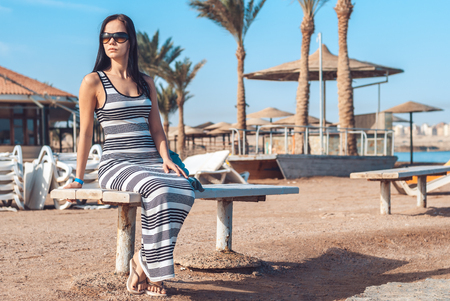 beautiful girl in a striped long dress and sunny goggles sits on a wooden bench against the background of an exotic sandy beach with palm trees, sun beds and sunny protective umbrellas Stok Fotoğraf
