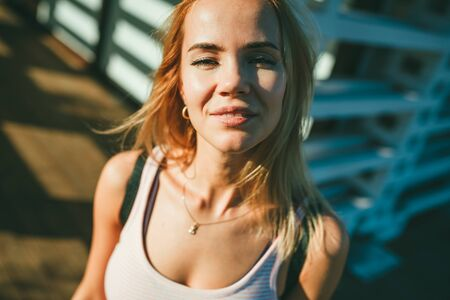 Portrait of a beautiful blond girl. She she smiles and squints in the sun on a blurred background of wooden structures and bright spots of the light and shadows