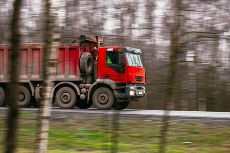 Red truck moving on a highway and in a hurry to deliver goods on time Banco de Imagens
