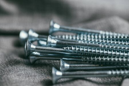A handful of metallic self-cutters screws lies against the backdrop of an old denim fabric. Selective focus macro shot with shallow DOF.