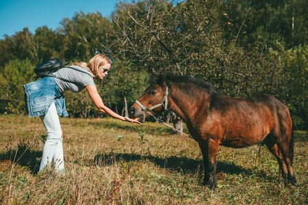 Long-haired beautiful young blonde woman in a pink T-shirt, light blue jeans and tied at the hips denim jacket, bent over and feeding an apple to a brown pony in the park over background of the apple orchard. On her back hangs a black leather backpack