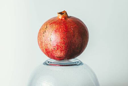 ripe red pomegranate on an inverted glass bowl. Healthy vegetarian food.