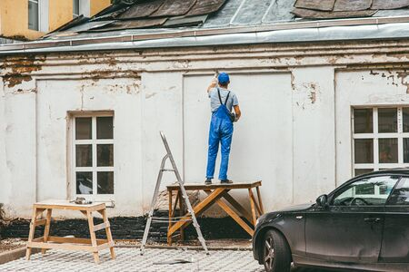 unrecognizable worker in blue construction pants stands on a wooden stand and works with a spatula with plaster on the wall. Renovation of the buildings facade on the street Foto de archivo