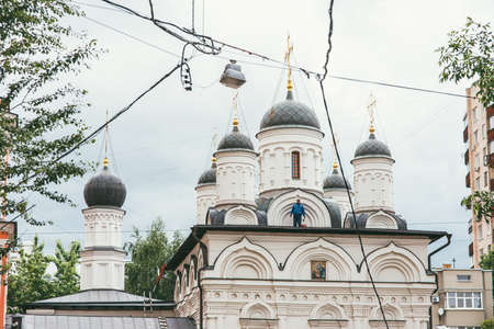 Moscow, Russia - JULY 7, 2017: Male caucasian worker in a blue overalls is repairing the roof of an Orthodox church in Moscow