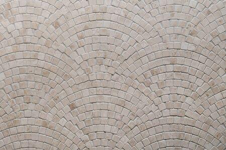 Beige mosaic tile texture on the bathroom wall.